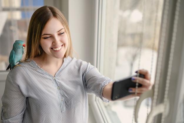 Dość młoda kobieta z telefonem komórkowym przy oknie, z papugą na ramieniu. wysokiej jakości zdjęcie