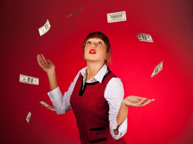 Dość młoda kobieta zaskoczony z wyciągniętymi ramionami patrzy na lecącego dolara