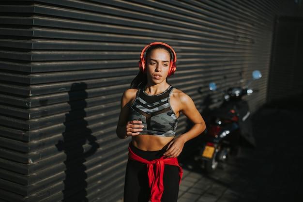 Dość młoda kobieta ze słuchawkami biegnącymi w pobliżu ściany na ulicy miasta