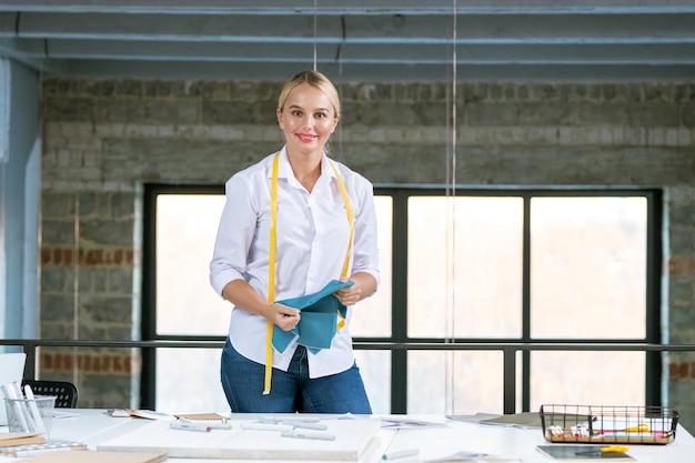 Dość młoda, kreatywna projektantka patrzy na ciebie stojąc przy biurku podczas pracy z próbkami tekstyliów w studio