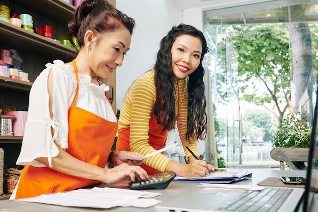 Dość młoda kwiaciarka pomaga współpracownikowi w księgowości, sprawdzaniu rachunków i wypłat po zamknięciu sklepu