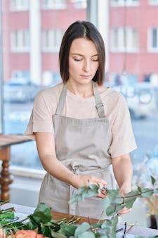 Dość młoda kwiaciarnia w odzieży roboczej stoi przy miejscu pracy i sortuje świeże kwiaty w pęczek