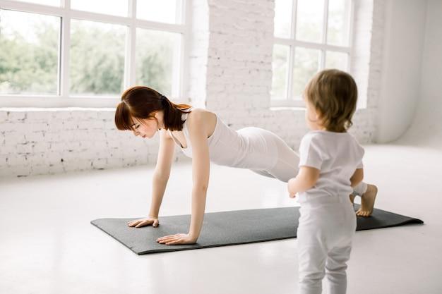 Dość młoda matka pasuje i gra w jogi, robiąc deskę, aby schudnąć wraz z małym dzieckiem w dużej lekkiej siłowni