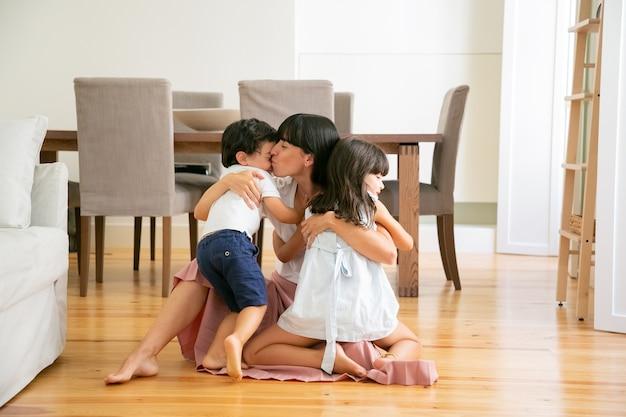 Dość młoda matka siedzi na podłodze i obejmując dzieci. szczęśliwa kaukaska mama z zamkniętymi oczami całuje syna i przytula córkę z miłością. pojęcie macierzyństwa, weekendu i rodzicielstwa