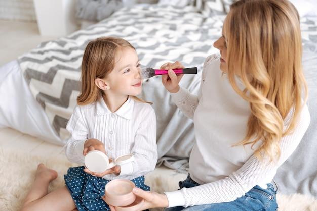 Dość młoda matka trzyma pędzel i nakłada nim proszek na nos swojej uśmiechniętej córki, ciesząc się procesem
