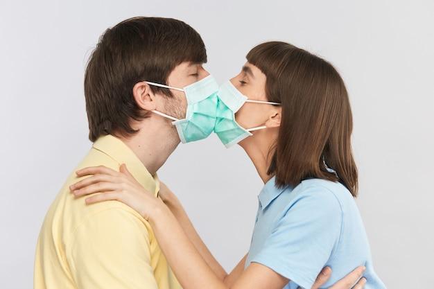 Dość młoda para całuje się w maskach ochronnych podczas pandemii koronawirusa, szczęśliwy facet i dziewczyna całują się w sterylnej masce