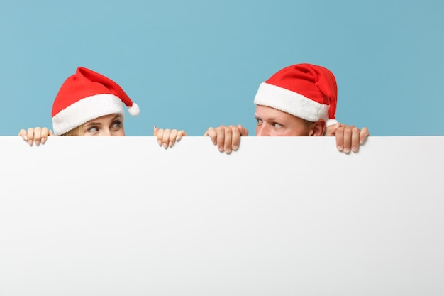 Dość młoda para przyjaciół santa, facet i kobieta w świątecznym kapeluszu