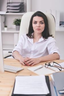 Dość młoda poważna bizneswoman lub szef firmy patrząc na ciebie siedząc w fotelu przy biurku przed kamerami