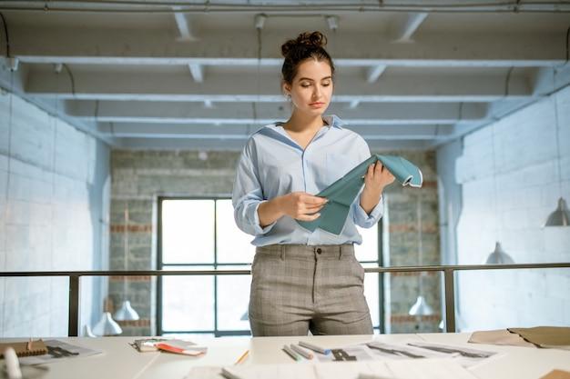 Dość młoda projektantka ubrań, która trzyma próbkę tekstyliów przy wyborze tkaniny do nowej kolekcji mody