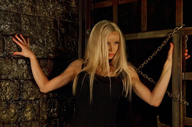 Dość młoda seksowna blondynka w czarnym stroju we wnętrzu średniowiecznego ciemnego pokoju z klatkami i łańcuchami na tle starej tekstury ściany. obraz królowej nocy horroru halloween. skopiuj miejsce