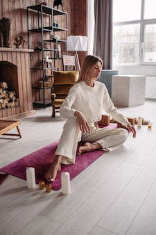 Dość młoda spokojna kobieta medytuje relaksujący, siedząc na naturalnej macie w przytulnym wnętrzu domu w weekend. wellness kobiety.