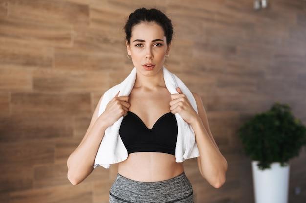 Dość młoda sportsgirl stojąca z ręcznikiem na ramionach