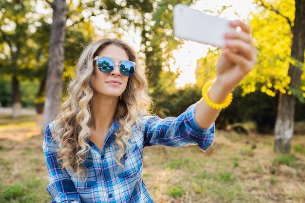 Dość młoda stylowa atrakcyjna uśmiechnięta blond kobieta siedzi w parku, styl casual lato