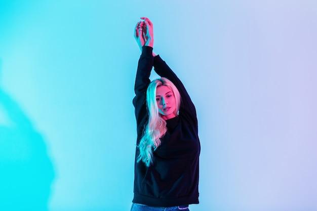 Dość młoda stylowa dziewczyna z blond włosami w modnej czarnej bluzie z kapturem na wielobarwnym różowo-neonowym tle sztuki