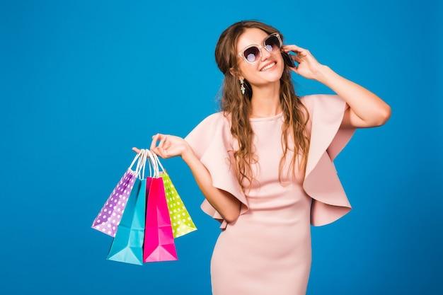 Dość młoda stylowa kobieta w różowej luksusowej sukience, używająca telefonu komórkowego i trzymającego torby na zakupy