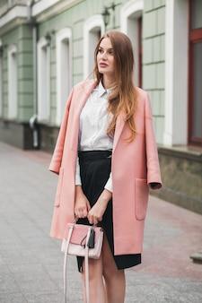Dość młoda stylowa piękna kobieta idąca ulicą, ubrana w różowy płaszcz, torebkę, białą koszulę, czarną spódnicę, strój modowy, trend jesienny, uśmiechnięty szczęśliwy, akcesoria