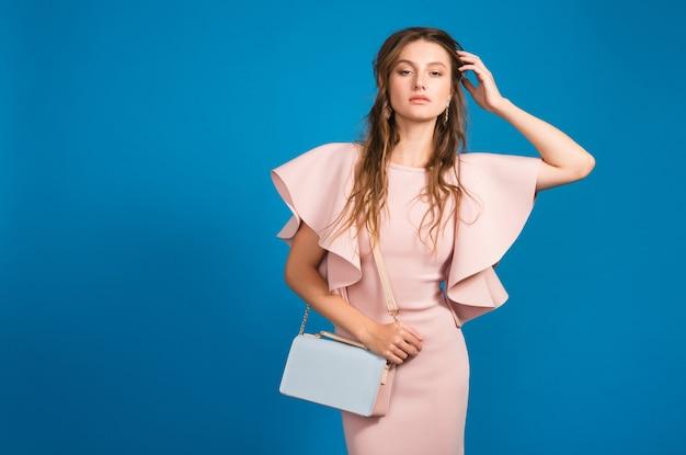 Dość młoda stylowa seksowna kobieta w różowej luksusowej sukience, letni trend w modzie, elegancki styl, niebieskie tło studio, trzymając modną torebkę