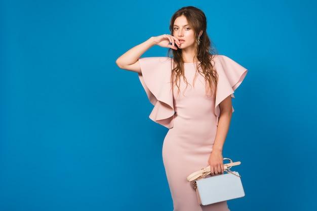 Dość młoda stylowa seksowna kobieta w różowej luksusowej sukience, letni trend w modzie, elegancki styl, trzymając modną torebkę