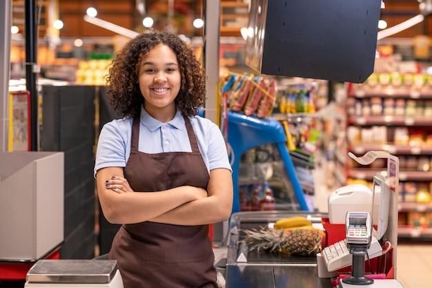 Dość młoda uśmiechnięta afroamerykańska sprzedawczyni płci żeńskiej z rękami skrzyżowanymi na piersi, patrząc na ciebie przez kasę podczas pracy