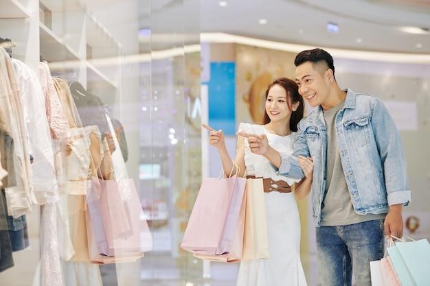 Dość młoda uśmiechnięta kobieta azji prosi chłopaka o zakup nowej sukienki w oknie sklepu butiku mody