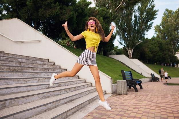 Dość młoda uśmiechnięta kobieta bawiąca się w parku miejskim, skacząca po schodach, pozytywna, emocjonalna, ubrana w żółty top, mini spódniczka w paski, różowe okulary przeciwsłoneczne, białe trampki, trend w modzie na lato