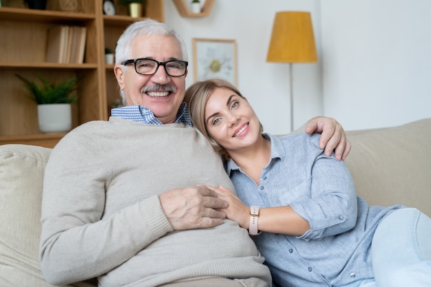 Dość młoda uśmiechnięta kobieta i jej szczęśliwy starszy ojciec patrząc na ciebie, relaksując się na kanapie w środowisku domowym