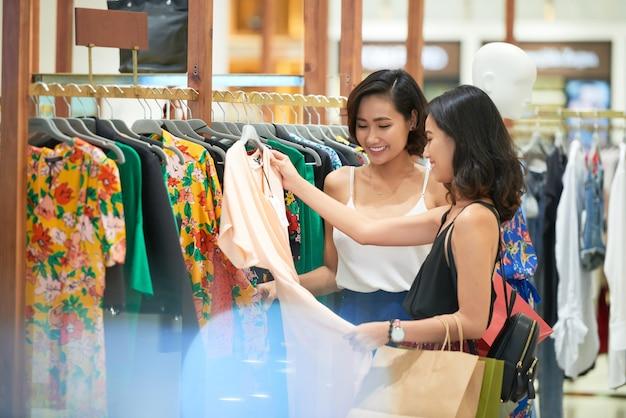 Dość młode koleżanki kupują idealną sukienkę w sklepie
