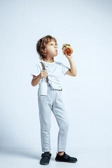 Dość młody chłopak kręcone w ubranie na białej ścianie. jedzenie burgera z butelką mleka. kaukaski męski przedszkolak z jasnymi emocjami twarzy. dzieciństwo, ekspresja, zabawa, fast food.