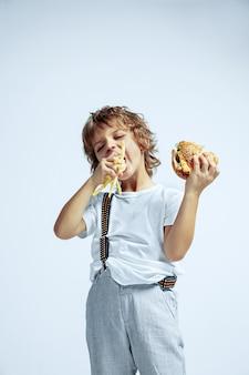 Dość młody chłopak kręcone w ubranie na białej ścianie. jedzenie burgera ze smażonym ziemniakiem. kaukaski męski przedszkolak z jasnymi emocjami twarzy. dzieciństwo, ekspresja, zabawa, fast food.