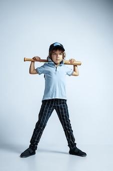 Dość młody chłopak kręcone w ubranie na białej ścianie. pewny siebie i fajny ze sportowym nietoperzem. kaukaski męski przedszkolak z jasnymi emocjami twarzy. dzieciństwo, ekspresja, zabawa.