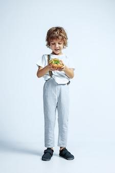 Dość młody chłopak kręcone w ubranie na białej ścianie studio. jedzenie burgera