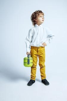 Dość młody chłopak w ubranie na białej ścianie. kaukaski mężczyzna przedszkolak z jasnymi twarzy emocji, trzymając worek na lunch. dzieciństwo, ekspresja, zabawa. wygląda poważnie, marzycielsko.