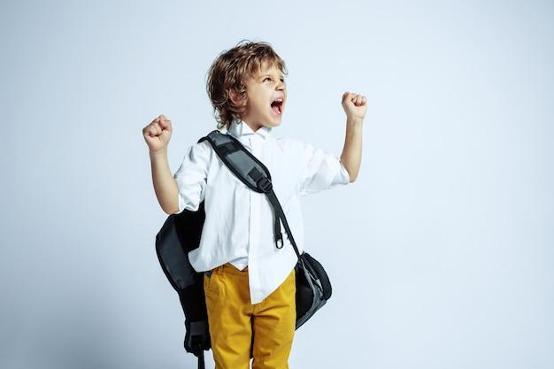 Dość młody chłopak w ubranie na białej ścianie. modne pozowanie. kaukaski męski przedszkolak z jasnymi emocjami twarzy. dzieciństwo, dobra zabawa. ekspresyjne emocje, krzyki.
