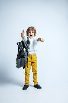 Dość młody chłopak w ubranie na białej ścianie. modne pozowanie. kaukaski męski przedszkolak z jasnymi emocjami twarzy. dzieciństwo, dobra zabawa. pozowanie z plecakiem. wskazywanie.