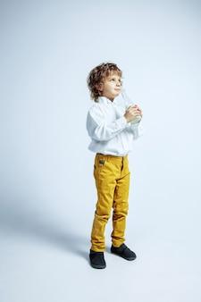 Dość młody chłopak w ubranie na białej ścianie. modne pozowanie. kaukaski męski przedszkolak z jasnymi emocjami twarzy. dzieciństwo, ekspresja, zabawa. pijąc mleko, ciesząc się,