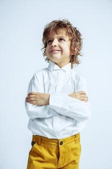 Dość młody chłopak w zwykłych ubraniach na białej ścianie studia studio