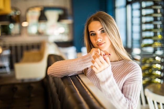 Dość młody model student nastolatka ubrana w dżinsy w kawiarni trzyma filiżankę kawy i herbaty w dłoniach