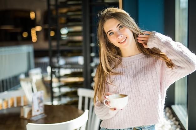 Dość młody model student nastoletnia pani ubrana w dżinsy ubrania w kawiarni trzyma w rękach filiżankę kawy i herbaty