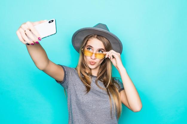 Dość młody model w t-shirt moda, kapelusz i okulary przezroczyste z telefonem w dłoniach sprawia, że selfie na białym tle na zielonym tle