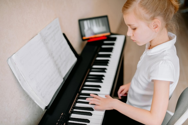 Dość młody muzyk grający na klasycznym pianinie cyfrowym w domu podczas zajęć online w domu.