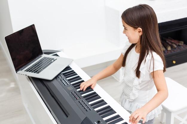 Dość młody muzyk grający w domu na klasycznym pianinie cyfrowym podczas zajęć online w domu, dystans społeczny podczas kwarantanny, samoizolacja, koncepcja edukacji online