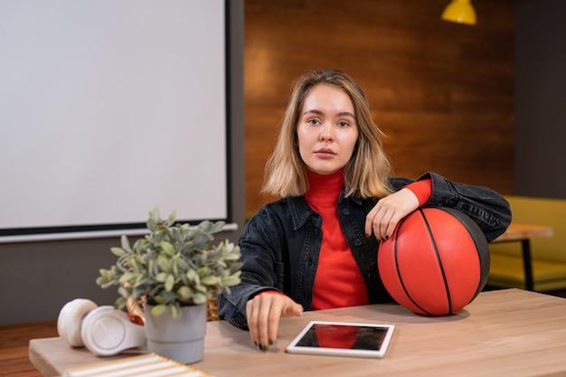 Dość młody student dorywczo z piłką i cyfrowym tabletem siedzi przy stole w kawiarni uczelni po zajęciach i czeka na przyjaciół