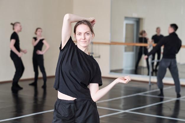 Dość młody student kursu tańca współczesnego baletu w czarnej odzieży sportowej stojącej podczas wykonywania ćwiczeń