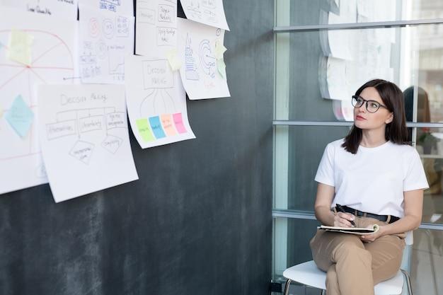Dość młody student lub bizneswoman siedzi na krześle i robienie notatek, patrząc na dokumenty na tablicy