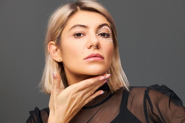 Dość modna blondynka z modnym efektownym makijażem pozuje na białym tle trzymając dłoń pod brodą, pokazując schludne wypolerowane paznokcie z pewnym enigmatycznym wyrazem twarzy