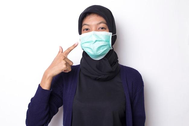 Dość muzułmańska młoda azjatka z medyczną maską ochronną do ochrony infekcji przed koronawirusem na odosobnionej białej przestrzeni