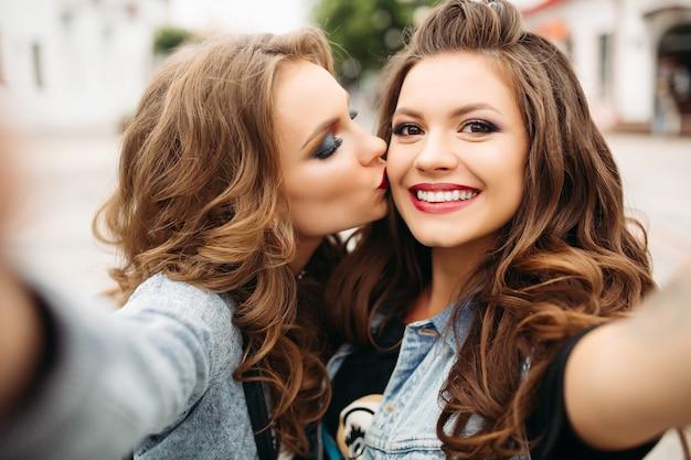 Dość nastolatki z fryzurami i czerwonymi ustami uśmiecha się do kamery.