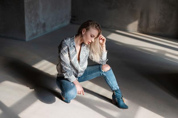 Dość nowoczesna blondynka młoda kobieta w stylowej letniej koszuli w niebieskie dżinsy zgrywanie w modnych kowbojskich butach, pozowanie, siedząc w pomieszczeniu z promieniami słonecznymi