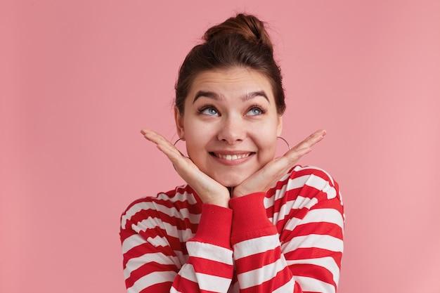Dość piękna młoda kobieta z piegami patrzy na bok, trzyma obie ręce na policzkach, ubrana w t-shirt w paski na różowo