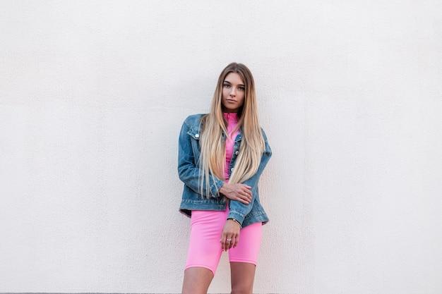 Dość piękna młoda kobieta ze wspaniałymi długimi włosami w niebieskiej stylowej dżinsowej kurtce w efektownym różowym kombinezonie sportowym pozuje w pobliżu budynku w mieście. seksowny atrakcyjna blondynka. styl retro.